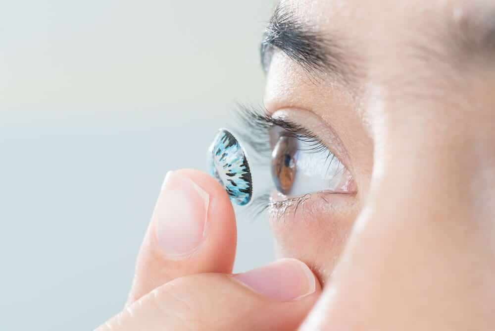 Young asian woman putting colored contact lens in her right eye, close up, selective focus at contact lens.
