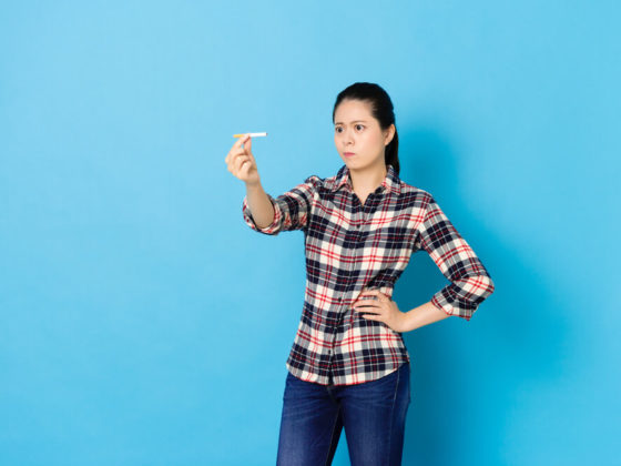 A woman looking confused at her cigarette wondering how long does nicotine stay in your system. Set against blue background.