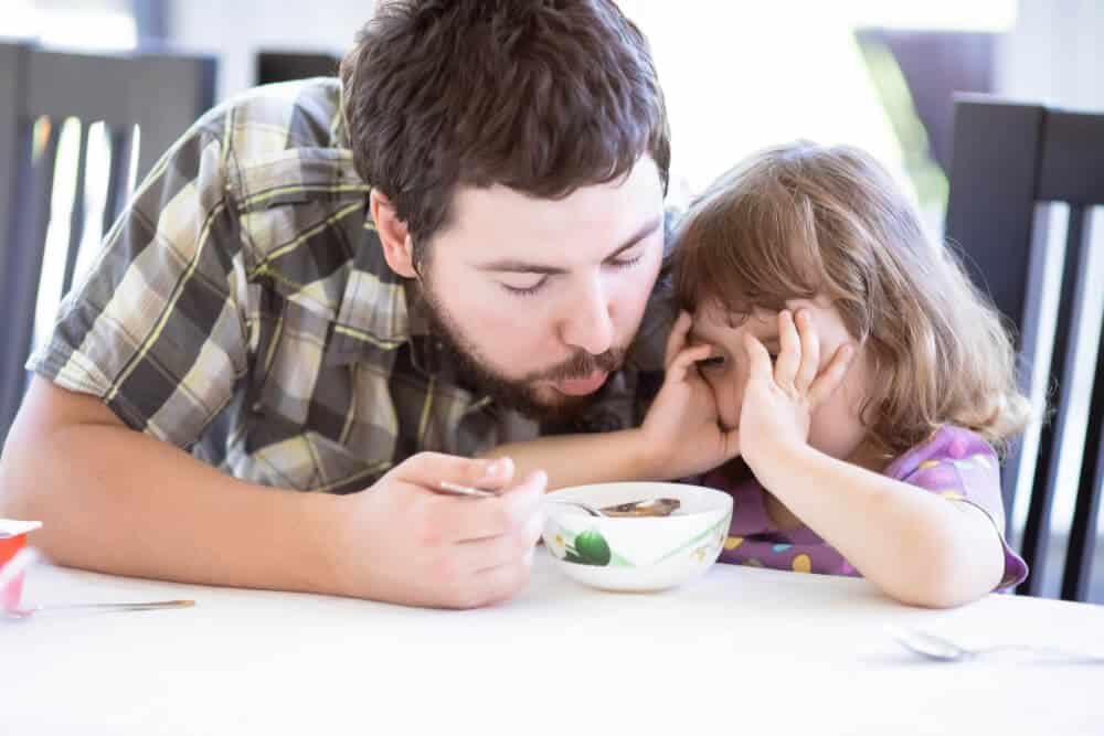 Father feeds his daughter and she doesn't want to eat. Kid refusing food. Negative reinforcement concept.