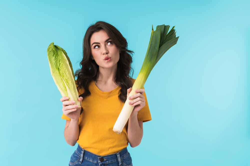 Image of thinking young beautiful woman posing isolated over blue wall background holding cabbage and leek, two nitric oxide foods.