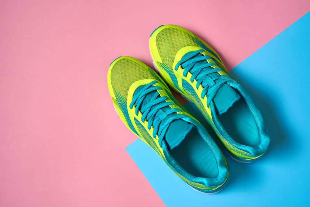 Pair of sport shoes on colorful background. New sneakers on pink and blue pastel background. Overhead shot of running shoes. Top view, flat lay
