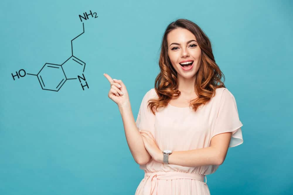 A happy woman points to a molecule of serotonin, isolated against blue background. Natural serotonin boosters concept.
