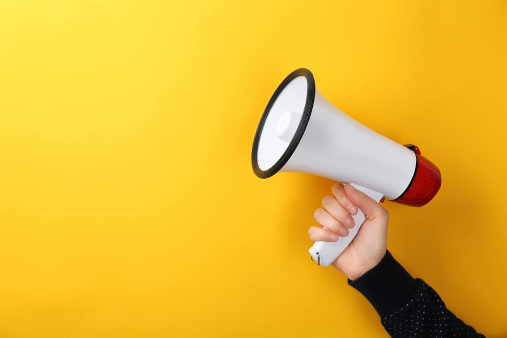 A woman holding a white megaphone in front of a yellow background.
