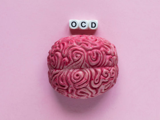 """OCD vs OCPD - A pink brain with black and white letter beads spelling """"OCD"""" on top of it in front of a light pink background"""