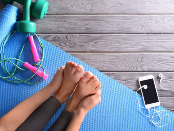 A woman stretching her legs on a blue yoga mat with her phone, weights and a jump rope