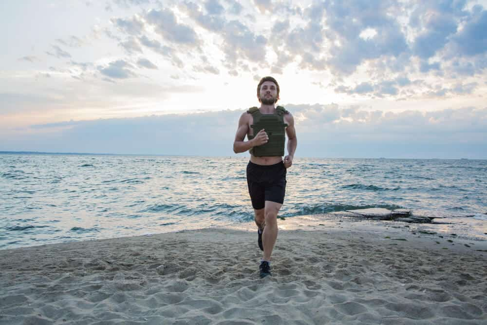 A man running with a weight vest on the beach