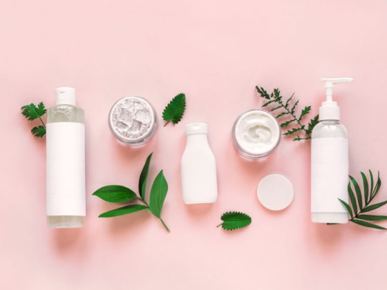 White skincare bottles with green leaves on a light pink background.