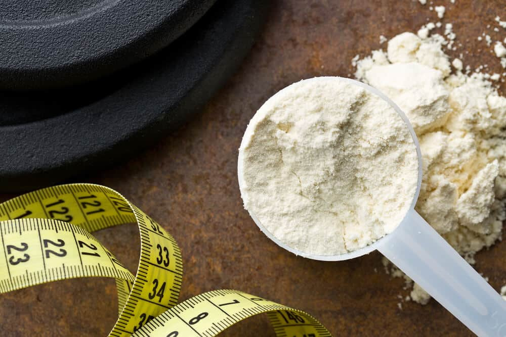 A scoop of white whey protein on a brown counter with yellow and black measuring tape and a black weight.