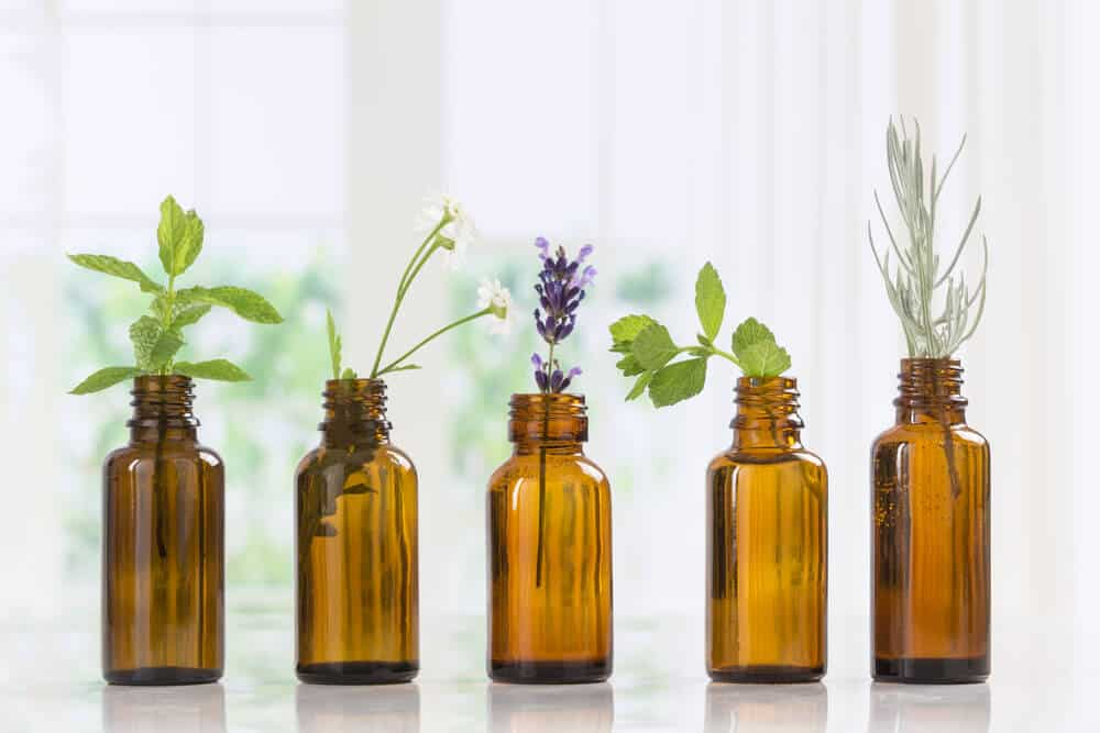 Five brown essential oil bottles with green herbs in them.