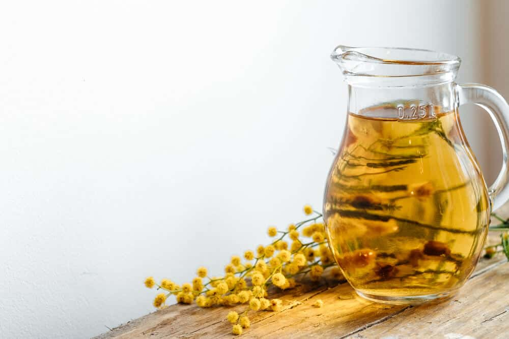 A clear pitcher with homemade yellow kombucha and yellow flowers on a table.