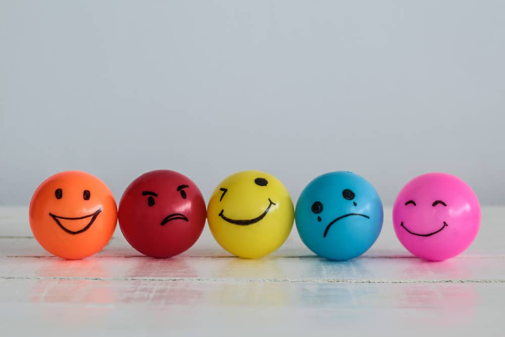 Four ping pong balls in different colors wearing different emotions.