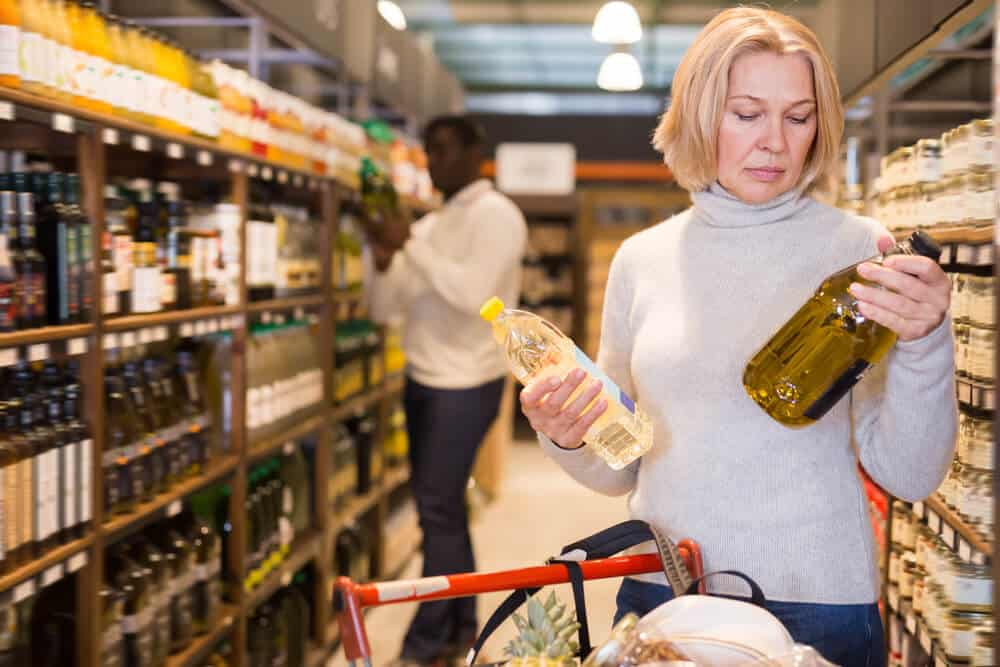 Attentive woman making purchases in store, choosing substitutes for vegetable oil