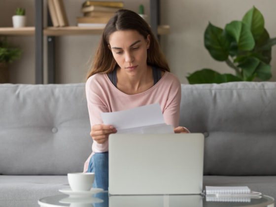 A woman sitting on a couch with a rejection letter in her hand and a coffee cup and laptop on the table in front of her.