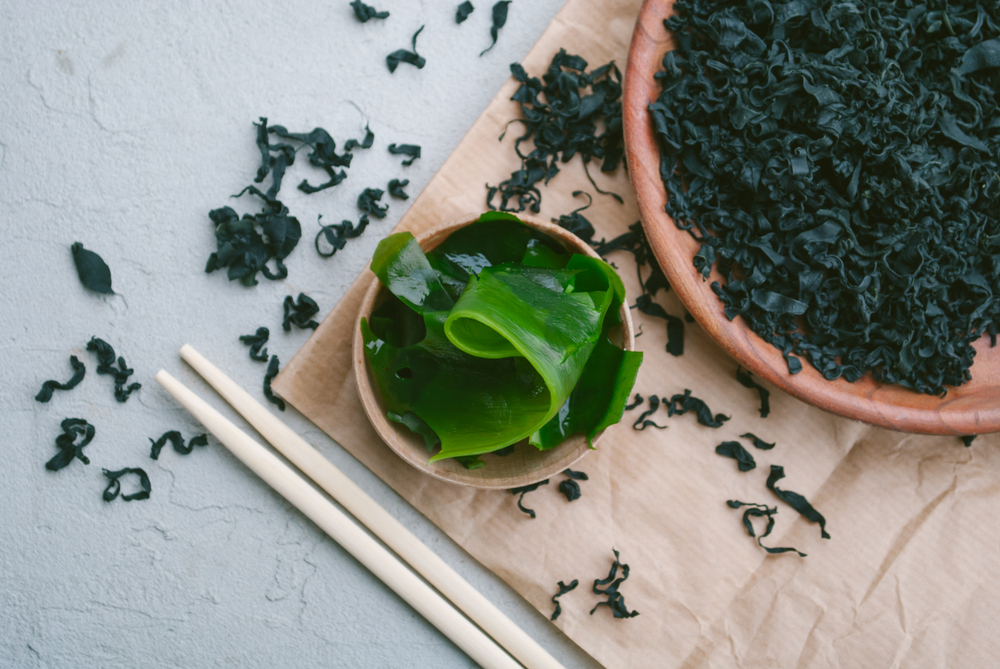 Wakame in two bowls with chopsticks.