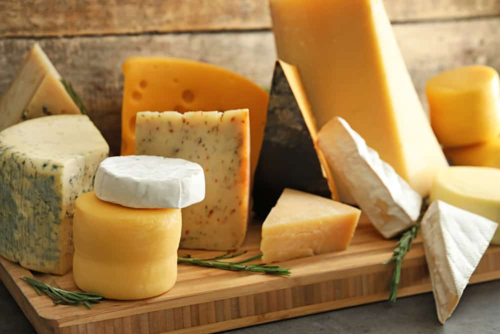 An assortment of yellow and white cheeses on a wooden block.